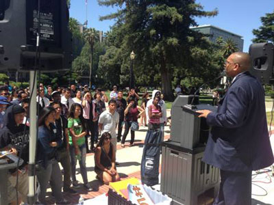 Rev. Billy Dixon talks in front of a crowd at the state capitol about the need for equitable education.